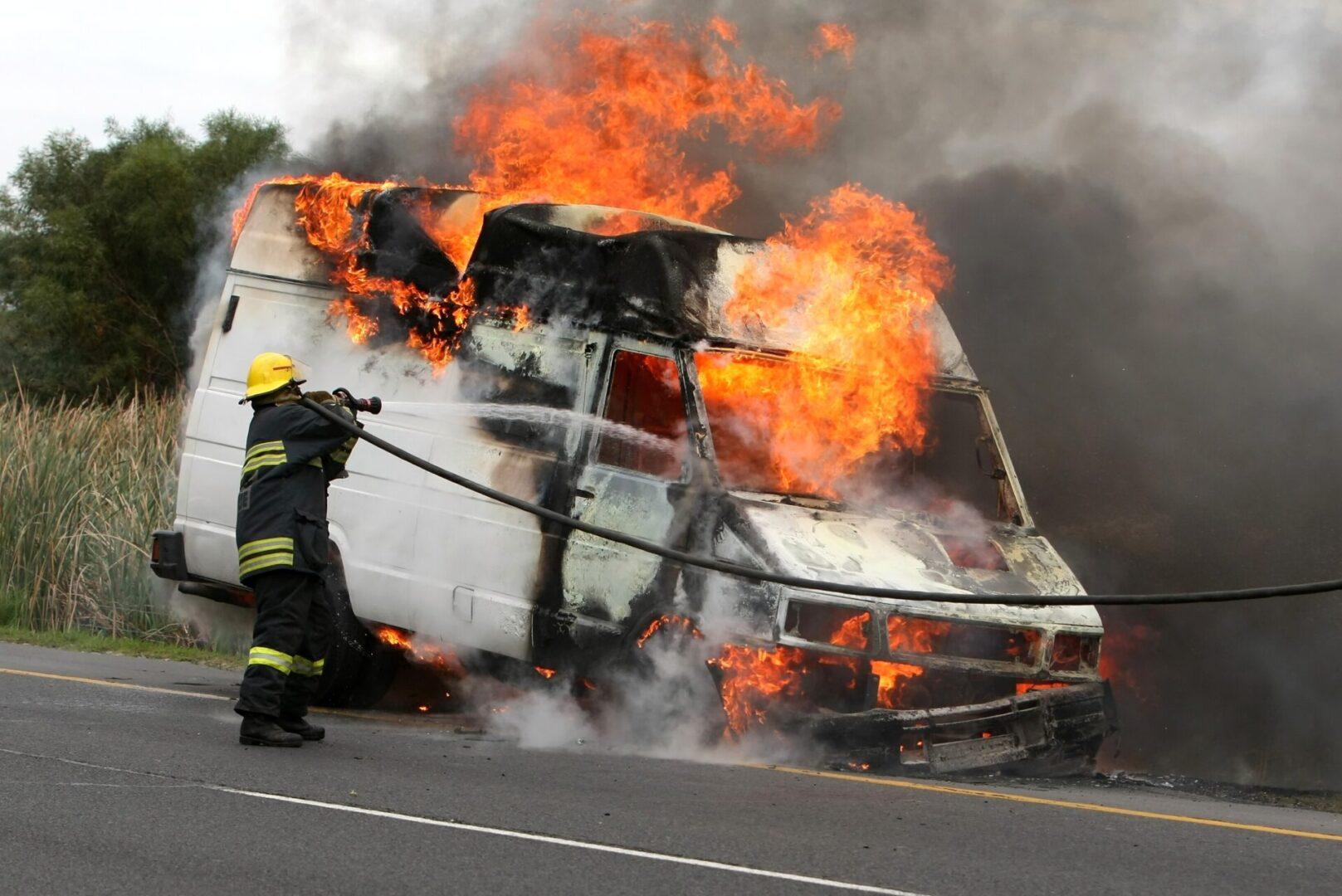 A fireman extinguishing a burning van